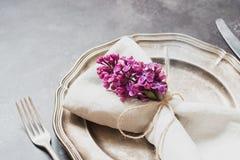 Fjädra den eleganta tabellställeinställningen med den violetta lilan, bestick på tappningtabellen close upp arkivfoton