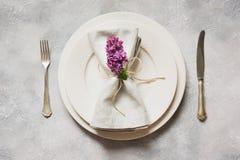 Fjädra den eleganta tabellställeinställningen med den violetta lilan, bestick på tappningtabellen ovanför sikt arkivbilder