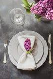 Fjädra den eleganta tabellställeinställningen med den violetta lilan, bestick på tappningtabellen ovanför sikt royaltyfri foto
