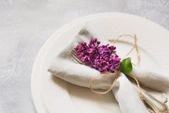Fjädra den eleganta tabellställeinställningen med den violetta lilan, bestick på tappningtabellen ovanför sikt arkivfoton