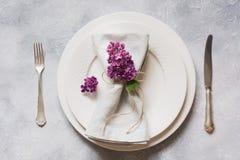 Fjädra den eleganta tabellställeinställningen med den violetta lilan, bestick på tappningtabellen ovanför sikt royaltyfri bild
