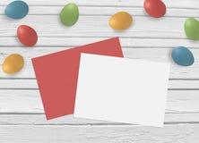 Fjädra, easter åtlöje upp plats med färgrika ägg, kuvertet, tomt papper och gammal vit träbakgrund, bästa sikt Arkivfoton