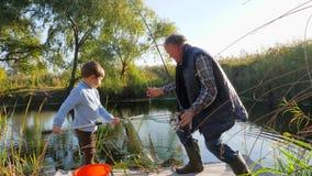 Fjädra fiske på fjorden, farfar med sonsonen har bra tid utomhus lager videofilmer