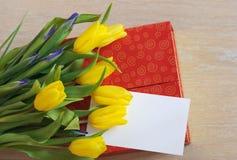 Fjädra gula tulpan, gåvan och vitbok som ligger på trä Royaltyfri Foto