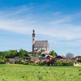 Fjädra landskap med den lantliga katolska kyrkan och den lilla bayerska byn arkivbild