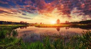Fjädra landskapet av ljus soluppgång över floden med färgrik molnig himmel på horisont Landskapvårnatur Royaltyfria Foton