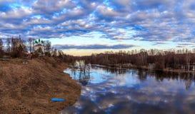 Fjädra landskapet, himmel, moln, tempel på banken av den översvämmade floden Arkivbild