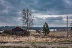 Fjädra landskapet i byn av Ryssland, med trähus och träd Arkivbild