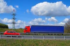 Fjädra landskapet med en huvudväg och en röd bilresande mot den röda lastbilen Fotografering för Bildbyråer