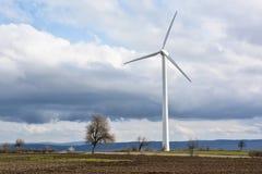 Fjädra landskapet med vindturbinen mot en molnig himmel Royaltyfria Foton