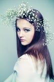 Fjädra ståendeflickan med kranen av blommor royaltyfri bild