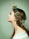 Fjädra ståendeflickan med kranen av blommor royaltyfria foton