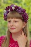 Fjädra ståenden av en flicka med en krans av blommor på hennes huvud Arkivfoto