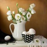 Fjädra stilleben med vitblommor och ägg arkivbild