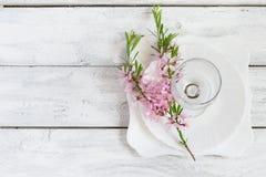 Fjädra tabellinställningen, den vita plattan och vinexponeringsglas som dekoreras med Royaltyfri Foto