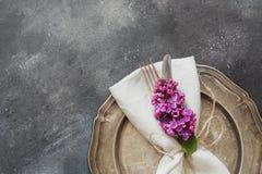 Fjädra tabellställeinställningen med den romanska violetta lilan, bestick på tappningtabellen ovanför sikt Royaltyfria Foton