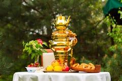 Fjädra tebjudningen i trädgården, på en tabell som täckas med en vit Royaltyfri Bild