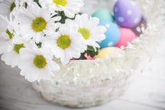 Fjädrar den närvarande korgen för påsken med vita blommor och kulöra ägg på träbakgrund inspiration Arkivfoto