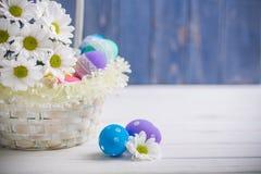 Fjädrar den närvarande korgen för påsken med vita blommor och kulöra ägg på träbakgrund inspiration Arkivbilder