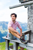 Fjällängar - man på berg som sitter på kabinen i tirol Fotografering för Bildbyråer