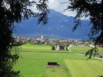 Fjällängarna - österrikisk by med den typiska kyrkliga tornspiran med berg Fotografering för Bildbyråer