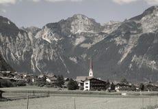 Fjällängarna - sikt av maxima för en by och bergi Österrike royaltyfri bild