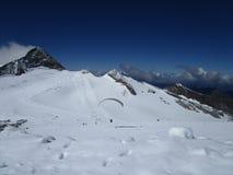Fjällängarna - steniga berg med insnöad sommar, Österrike, blå himmel med paraglideren royaltyfri bild