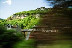 Fjällängberg och dolt hus som ses från snälltåget i rörelse Royaltyfri Fotografi