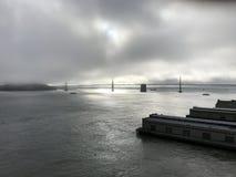 Fjärdbron i San Francisco, Kalifornien på gryning shrowded i dimma Arkivbild