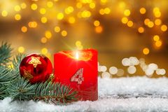 Fjärde advent som dekorerar med stearinljuset, bollen och gran i snön Royaltyfria Bilder