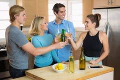 Fjärdedel av det Juli partiet med en grupp av vänkompisar som tillsammans rostar öl och har en beröm för husparti för gyckel Arkivbild