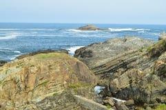 Fjärden med vågorna som bryter på dess, vaggar i bakgrunden en liten ö i Tapia De Casariego Natur lopp, rekreation royaltyfri fotografi