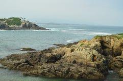 Fjärden med vågorna som bryter på dess, vaggar i bakgrunden som ett hus som döljas bland, vaggar i Tapia De Casariego Natur lopp, royaltyfria bilder