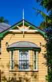 Fjärdfönster på det gula traditionella australierQueenslander huset med det tenn- taket och tropiska träd Arkivbilder