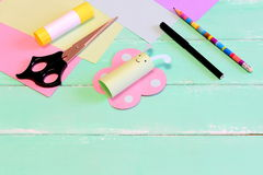 Fjärilen för roligt papper tillverkar, sax, markören, limpinnen, blyertspennan, färgat papper, blyertspenna på grön träbakgrund Arkivbild