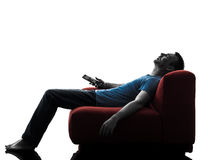 Fjärrkontroll för mansoffasoffa som sover hållande ögonen på tv Royaltyfri Fotografi