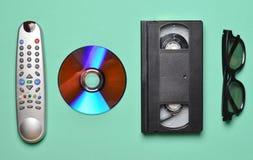 Fjärrkontroll från TV:N, 3d exponeringsglas, CD drev, vhs på bakgrund för mintkaramellfärgpastell Retro teknologi Royaltyfri Bild