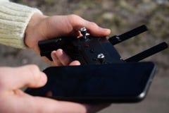 Fjärrkontroll och smartphone i manliga händer En man som rymmer en sändare och lotsar några medel Ett surr, radiosänder den kontr royaltyfria bilder