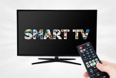 Fjärrkontroll som siktar den moderna smarta TVapparaten Arkivbild