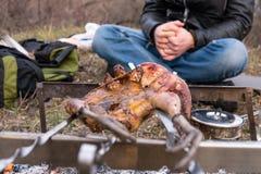 Fj?derf? f?rbereda sig som jagar tema Laga mat en hel fasankropp p? stekn?lar f?r ett j?rn ?ver en l?gereld med brinnande kol och royaltyfri bild