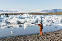 FJALLSARLON, ICELAND - AUGUST 2018: Man in orange jacket taking pictures of floating ice in Vatnajokull glacier lagoon royalty free stock photography