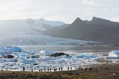 FJALLSARLON, ICELAND - AUGUST 2018: people walking on the shore of Vatnajokull glacier lagoon at sunset.  stock images