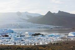FJALLSARLON, ISLAND - AUGUST 2018: Leute, die auf das Ufer der Vatnajokull-Gletscherlagune bei Sonnenuntergang gehen stockbilder