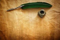 Fjäderpenna och färgpulver väl på pergamentpapper Royaltyfri Fotografi