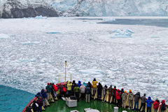 Fjiord, glaciers, ice, cruise. A crowd of adventure tourists gathered at the bow of a cruise (expedition) ship as it approaches the glaciers and icebergs in stock photo