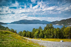 Fjord Landscape. Norway. Fjord landscape with beautiful clouds and road with stones in front. Norway Stock Photos