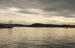 Fjord på solnedgången - Oslo, Norge, Europa; lynnigt och dystert royaltyfri bild