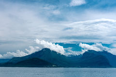 Fjord scene with hazy mountains and  cloudy sky Stock Photos