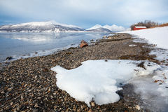 Fjord shore, natural winter landscape in Norway. Beach on a fjord surrounded by snowy mountains Stock Photography
