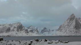 Fjord umgeben durch Winter-Berge und Wolken Wolken bewegen sich nah an der Gebirgsspitze stock footage